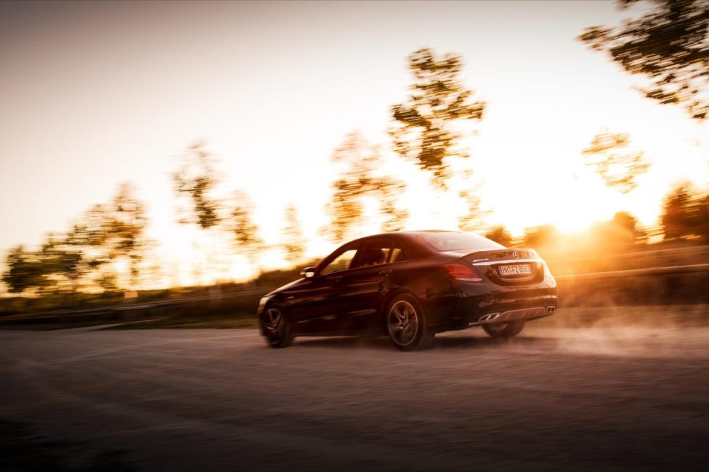 Mercedes C43 AMG dynamisch mit Staub im Sonnenuntergang Wallpaper